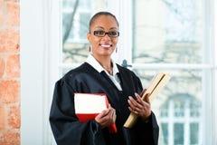 律师在有法律书籍和人事档案的办公室 免版税图库摄影
