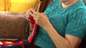 徒升资深祖母妇女坐沙发并且编织长袜 股票录像