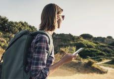 徒步旅行者一条供徒步旅行的小道的旅客妇女使用智能手机、旅行和活跃生活方式概念 库存图片