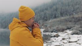 徒步旅行者人吹在手上的,冷天 在多雪的山的年轻旅客身分在美丽的湖附近 股票录像