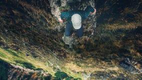 徒步旅行者人坐峭壁与山鸟瞰图旅行生活方式冒险假期概念的桥梁边缘 免版税库存照片