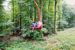 徒步旅行者在夏天使用滑雪电缆车转移重的齿轮山 免版税图库摄影