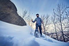 徒步旅行者在雪森林里走 库存图片