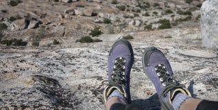 徒步旅行者坐岩石峭壁 库存照片