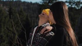 徒步旅行者夫妇一起坐在美丽的山的岩石 他们互相谈话,笑和获得乐趣 股票录像