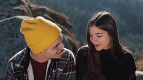 徒步旅行者夫妇一起坐在美丽的山的岩石 他们互相谈话,笑和获得乐趣 股票视频