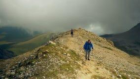 徒步旅行者夫妇父亲和儿子美好的风景的 徒步旅行者人和儿童迁徙的走与在足迹的背包在山 股票视频
