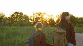徒步旅行者女孩,青少年的女孩旅行并且握手 儿童旅客 乡下公路的旅游女孩 有背包的女孩 股票视频