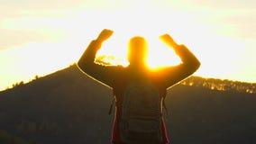 徒步旅行者旅游妇女剪影有胳膊的被举在看日落视图的山顶部 远足者女孩 旅客妇女 股票录像