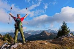 徒步旅行者欢呼兴高采烈和有福与在天空举的胳膊在远足以后 库存照片
