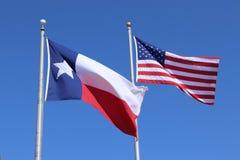 得克萨斯旗子、孤立星状态旗子和美利坚合众国美国旗子反对清楚的蓝天背景 免版税库存照片