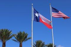 得克萨斯旗子、孤立星状态旗子和美利坚合众国美国旗子反对蓝天背景和棕榈树 库存图片