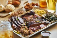 得克萨斯样式bbq盘子用熏制的胸肉,圣路易斯肋骨,拉扯了猪肉、鸡、热链接和边 免版税库存图片