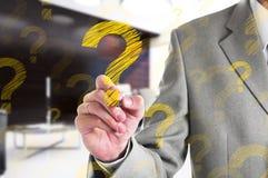 得出一个黄色问号的商人 到达天空的企业概念金黄回归键所有权 免版税图库摄影