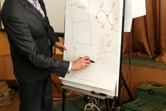 得出财政图的典雅的报告人讲师在白板 免版税库存图片