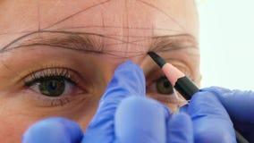得出microblading的美容师新的眼眉形状在女性面孔特写镜头 影视素材