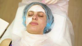 得到一种化妆医学治疗,特写镜头的年轻女人 美容师手在工作,清洗的皮肤,做脸部按摩 影视素材
