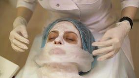 得到一种化妆医学治疗,特写镜头的年轻女人 美容师手在工作,清洗的皮肤,做脸部按摩 股票视频