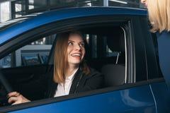 得到一辆新的汽车的钥匙的年轻微笑的妇女 出租汽车的概念 库存照片