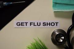 得到与启发和医疗保健/医疗概念的流感预防针在书桌背景 免版税库存照片