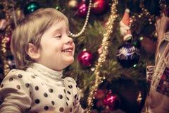 得到与圣诞树的愉快的微笑的孩子圣诞节礼物在减速火箭的样式的背景 免版税库存图片