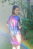 得到亚裔的孩子使用在庭院里和湿与水管 图库摄影