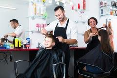 得到人的发型小学年龄的愉快的男孩 免版税库存照片