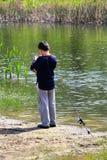 得到他的勾子的男孩准备好钓鱼 免版税库存照片