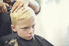 得到他的头发的逗人喜爱的白肤金发的男孩切开了在美容院 免版税库存图片