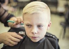 得到他的头发的逗人喜爱的白肤金发的男孩切开了在美容院 免版税库存照片