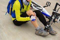 得到伤害,当落从在路时的登山车的骑自行车者 免版税图库摄影