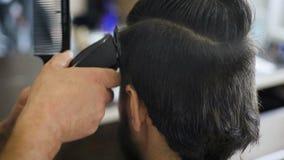 得到修饰 给理发的射击一位英俊的有胡子的理发师他的使用整理者的客户 影视素材