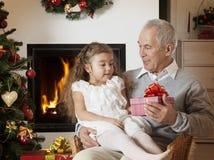 得到圣诞节礼物的愉快的小女孩 库存图片