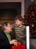 得到圣诞节礼物的年轻男孩从祖父 图库摄影