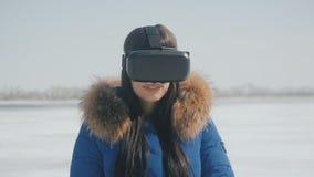 得到在使用的少妇画象VR耳机的经验室外在冬天 女孩使用一件虚拟现实盔甲 影视素材