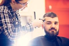 得到在现代理发店的英俊的年轻有胡子的白种人人画象时髦理发 免版税库存图片