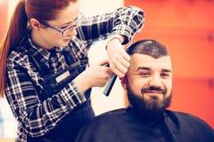 得到在现代理发店的英俊的年轻有胡子的白种人人画象时髦理发 免版税库存照片