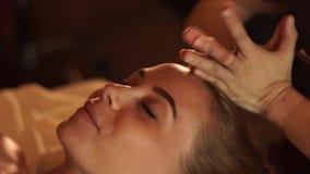 得到在秀丽温泉沙龙的年轻女人顶头按摩 接受在化妆用品的接近的画象妇女顶头皮肤按摩 股票视频