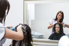 得到头发的妇女被上色在美容院 免版税库存照片