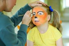 得到她的面孔的可爱的小女孩被绘象老虎由艺术家 免版税库存图片