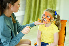 得到她的面孔的可爱的小女孩被绘象老虎由艺术家 免版税库存照片
