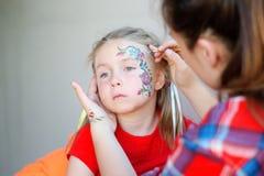得到她的面孔花的可爱的女孩被绘 库存图片