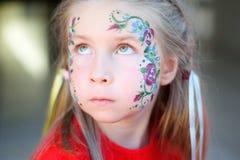 得到她的面孔花的可爱的女孩被绘 免版税库存图片