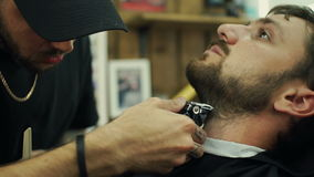 得到完善的形状 可及胡子理发的年轻有胡子的人特写镜头侧视图由美发师理发店 股票录像