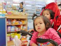 得到小的亚洲女婴的前面不耐烦等待在婴儿车的很长时间的她的母亲买的药物药房 免版税库存图片