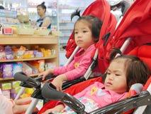 得到小的亚洲女婴的前面不耐烦等待在婴儿车的很长时间的她的母亲买的药物药房 免版税库存照片