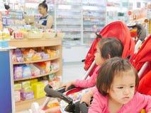 得到小的亚洲女婴的前面不耐烦等待在婴儿车的很长时间的她的母亲买的药物药房 库存图片