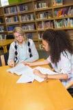 得到帮助的学生从家庭教师在图书馆里 免版税库存图片