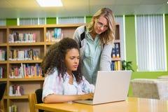 得到帮助的学生从家庭教师在图书馆里 免版税库存照片