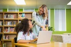 得到帮助的学生从家庭教师在图书馆里 库存照片